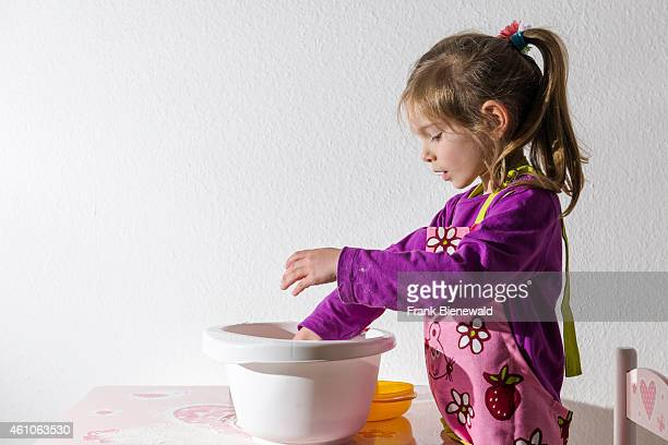 A blond three year old girl is baking Christmas cookies pouring ingredients into a white bowl