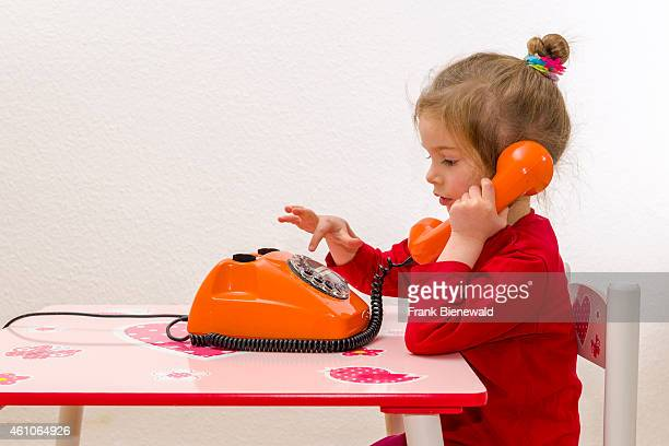 A blond three year old girl is sitting at a table and using an orange telephone