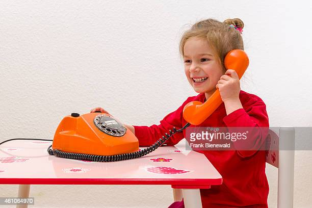 A blond three year old girl is sitting at a table and using an orange telephone smiling