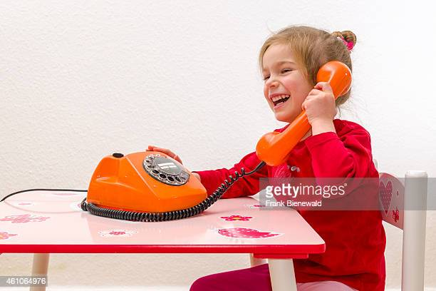 A blond three year old girl is sitting at a table and using an orange telephone loughing