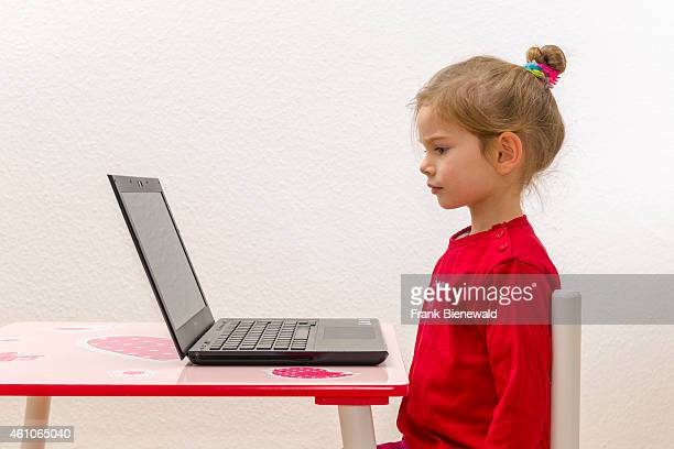 A blond three year old girl is sitting in front of a notebook laptop watching the screen
