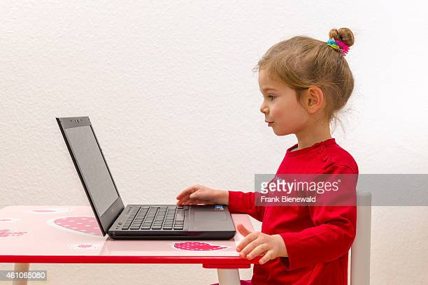 A blond three year old girl is sitting in front of a notebook laptop watching the screen and using the keyboard
