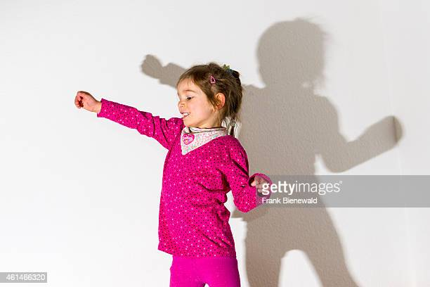 A blond three year old girl wearing a pink shirt is dancing in front of a white wall leaving her shadow behind her