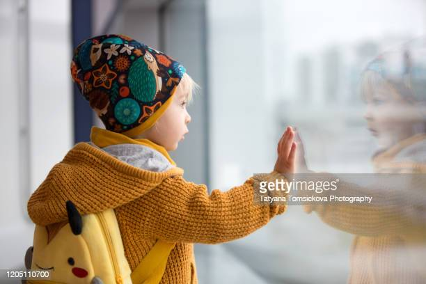 blond toddler boy with family, traveling with airplane, running at the airport with suitcase - leaving stock pictures, royalty-free photos & images