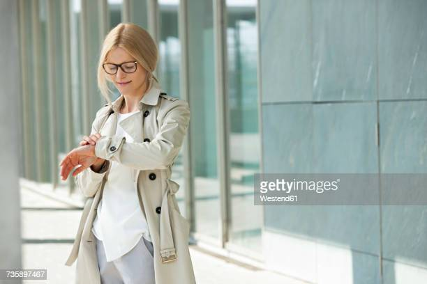 Blond woman checking the time