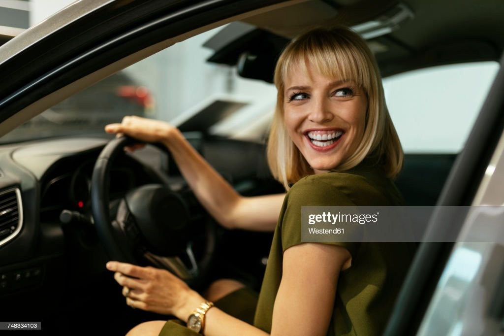 Blond woman choosing new car in car dealership : Stock Photo