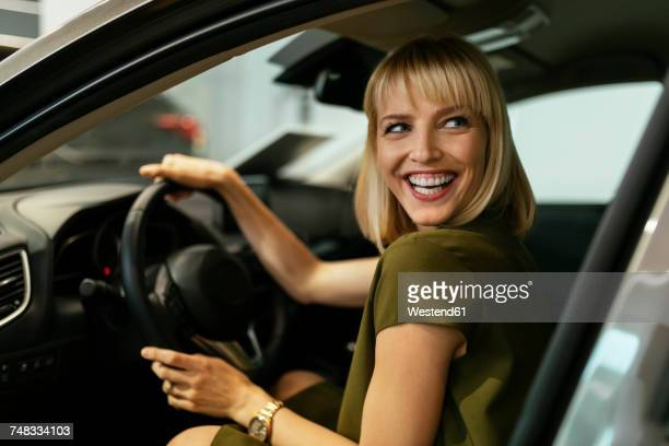 blond woman choosing new car in car dealership - test drive stock pictures, royalty-free photos & images
