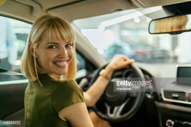 Blond woman choosing new car in car dealership
