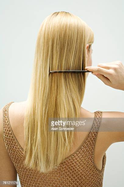 Blond woman combing her hair