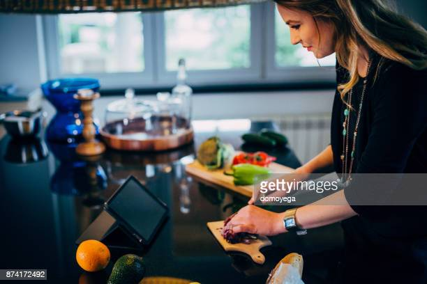 Blond woman cutting ingredients to make a healthy meal