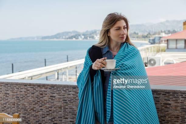 Blond woman drinking tea at seaside restaurant in Batumi