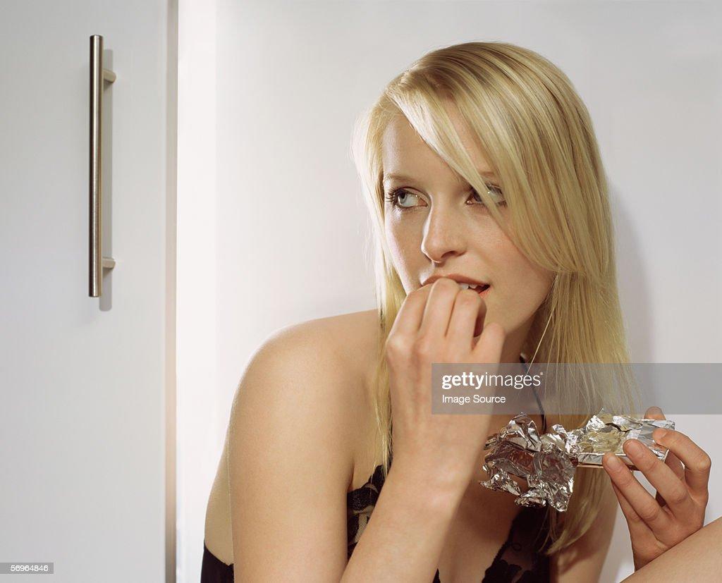 Blond woman eating chocolate bar : Stock Photo