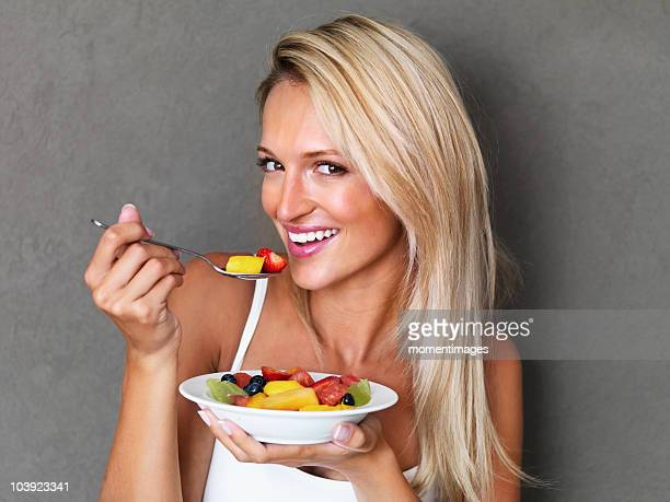 Blond woman eating fresh fruit salad