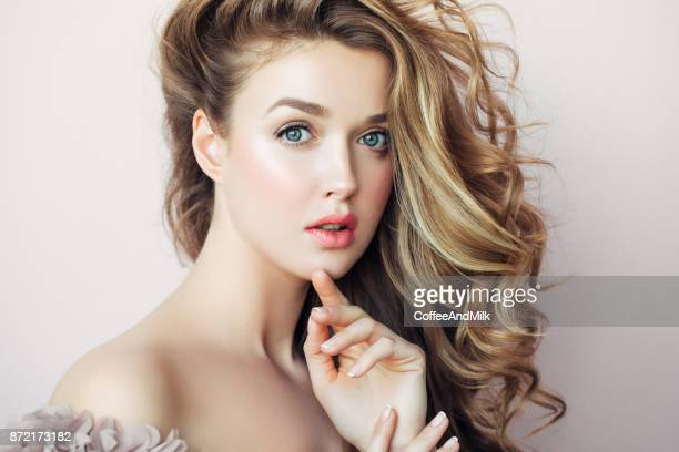 Blond woman fashion model posing against light background