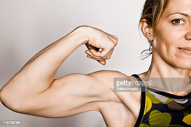 blond woman flexes bicep - flexing muscles stock pictures, royalty-free photos & images