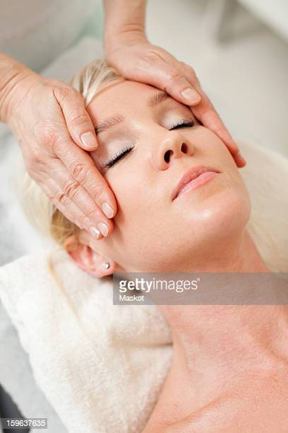 Blond woman getting a face massage from mature masseur at health spa