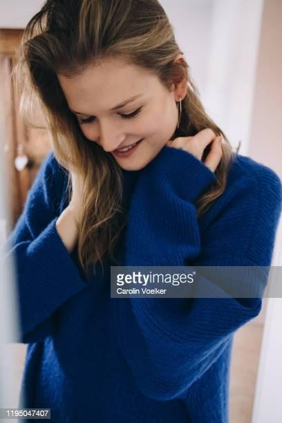 blond woman in a blue wool sweater looking down pulling her hair - blauwe jurk stockfoto's en -beelden