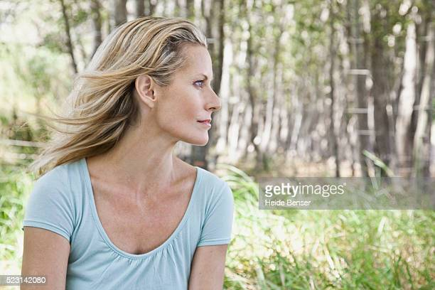 blond woman in forest clearing - mid adult stock pictures, royalty-free photos & images