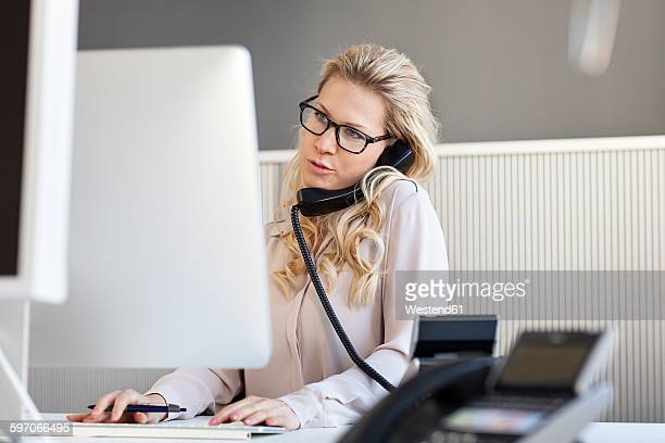 Blond woman in office on the phone
