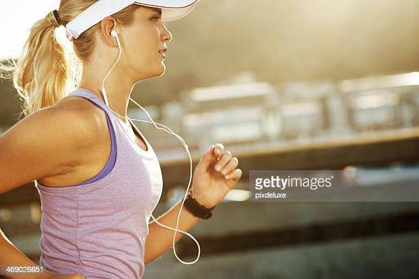 Blond woman jogging while wearing ear buds