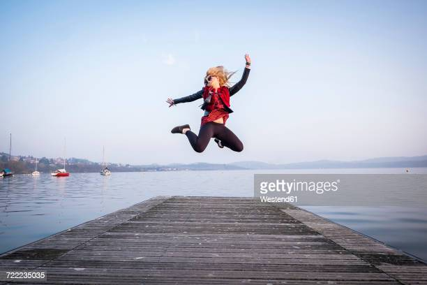 Blond woman jumping in the air on a jetty