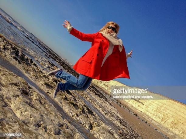blond woman jumping on rocky coastline - extra long stock pictures, royalty-free photos & images