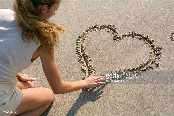 Blond woman painting a heart into the sand with her finger, high angle view