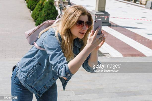 Blond woman photographing with smartphone