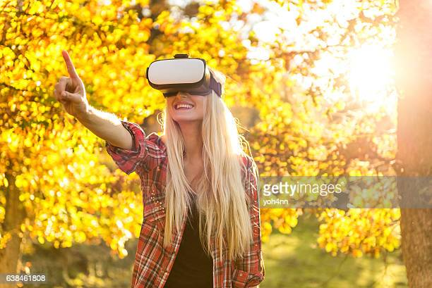Blond woman playing outdoors with VR headset