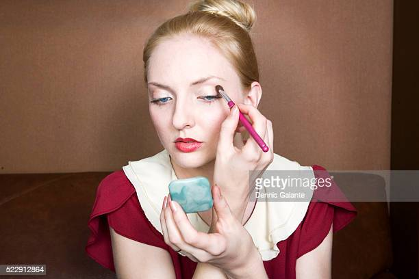 blond woman putting on eyeshadow - powder compact stock pictures, royalty-free photos & images