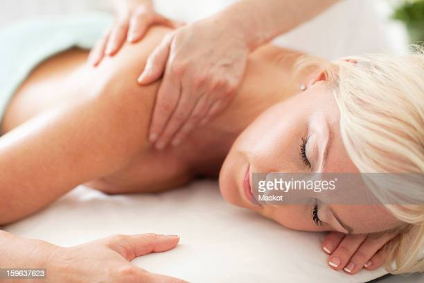 Blond woman receiving a shoulder massage at health spa