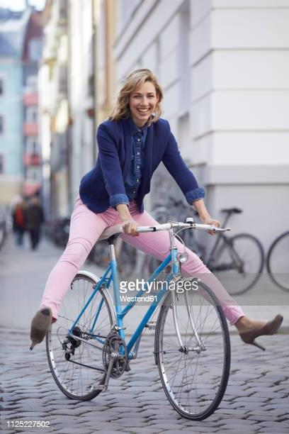 blond woman riding a bike in the city - adulto de mediana edad fotografías e imágenes de stock