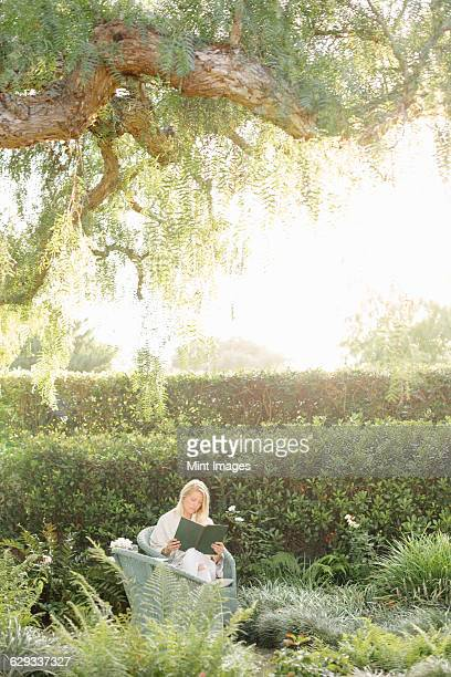 Blond woman sitting in a wicker chair in a garden, reading.