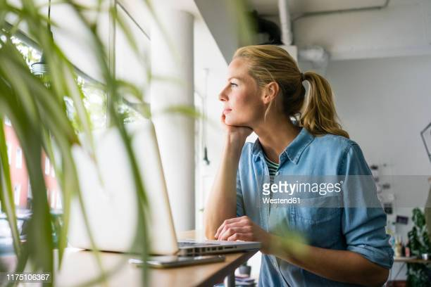 blond woman sitting in coffee shop, using laptop, looking out of window - looking at view stock pictures, royalty-free photos & images
