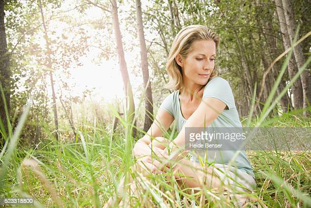 blond woman sitting in grass in forest - graspflanze stock-fotos und bilder