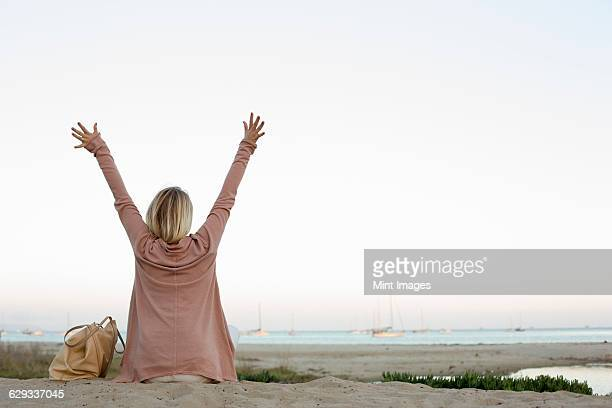 Blond woman sitting on a sandy beach, arms raised.