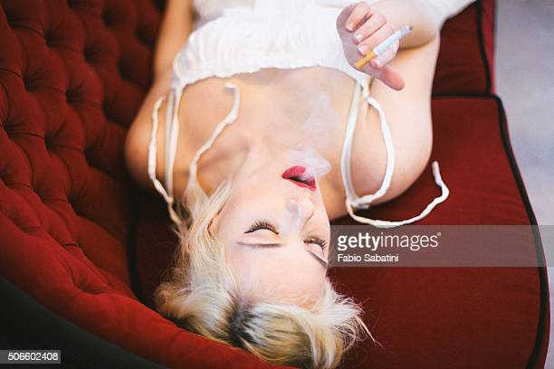 Blond woman smoking on red couch