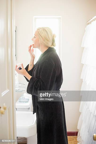 Blond woman standing in a bathroom, applying cream to her lips.