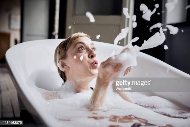 blond woman taking bubble bath blowing foam in the air - bubble bath stock pictures, royalty-free photos & images