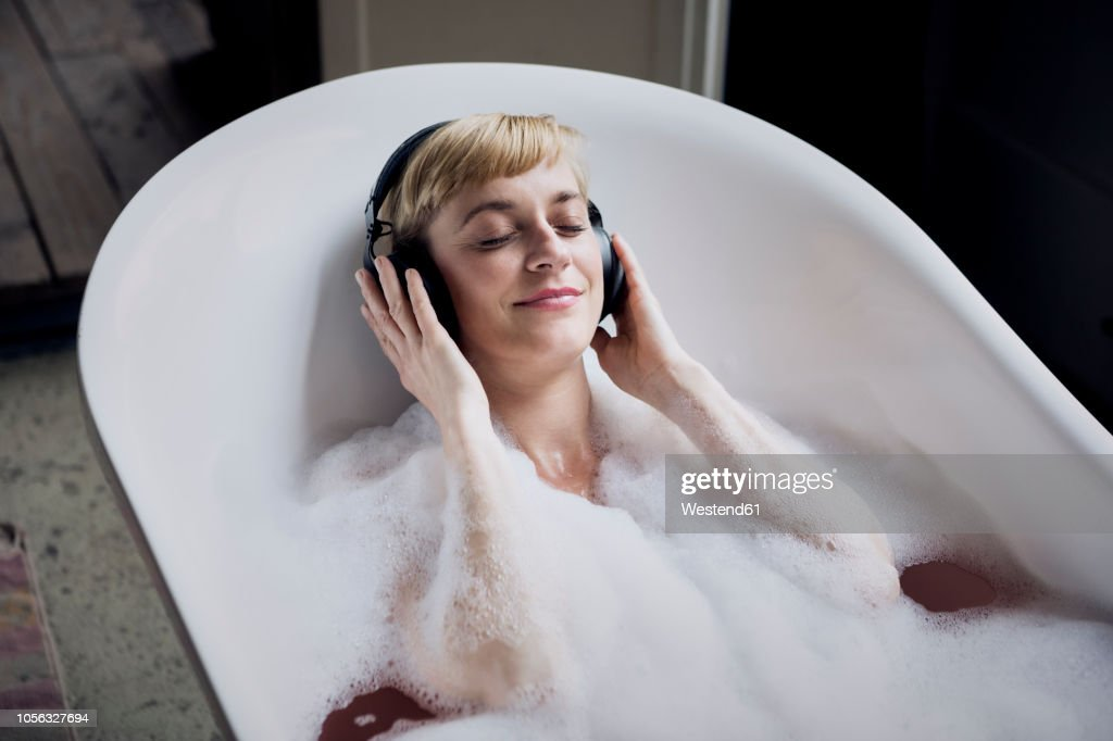 Blond woman taking bubble bath in a loft listenung music with headphones : Stock-Foto