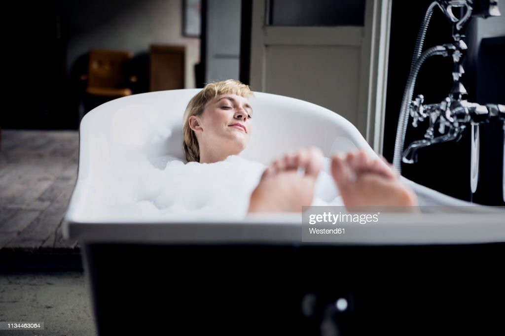 Blond woman taking bubble bath in a loft : ストックフォト