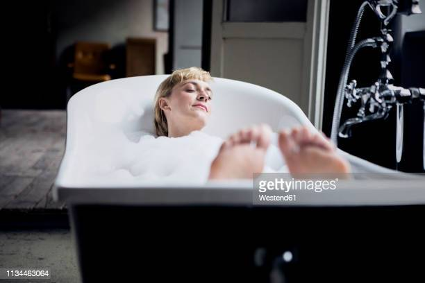 blond woman taking bubble bath in a loft - taking a bath stock pictures, royalty-free photos & images