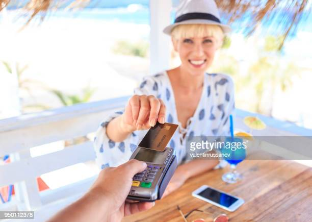 blond woman using credit card in beach cafe - commercial activity stock photos and pictures