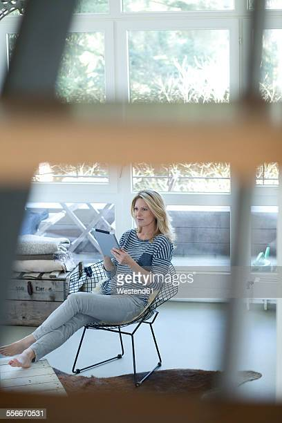 Blond woman using digital tablet at home