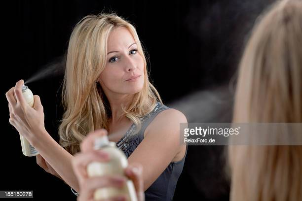 Blond woman using hairspray in front of mirror