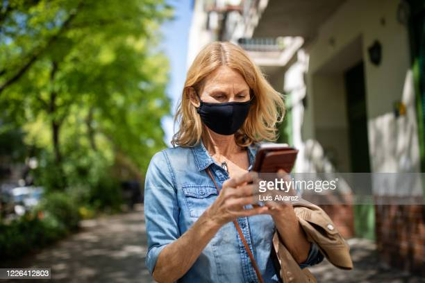 blond woman using smart phone in city during lockdown - abstand halten infektionsvermeidung stock-fotos und bilder