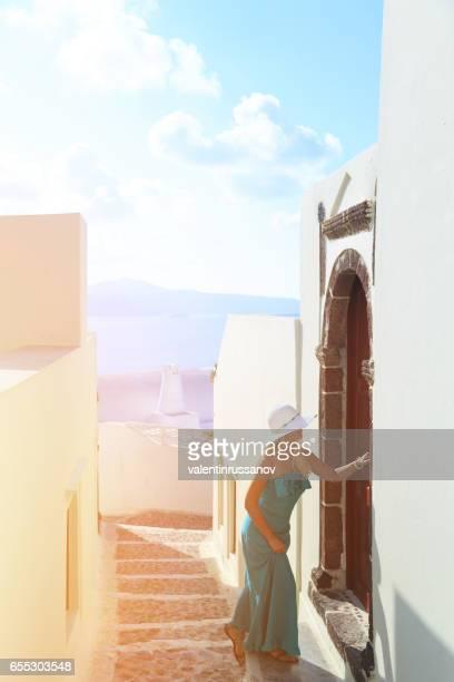 blond woman walking on street in santorini - oia santorini foto e immagini stock
