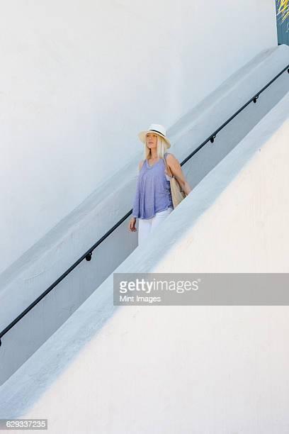 blond woman wearing a hat walking down a staircase. - down blouse stockfoto's en -beelden