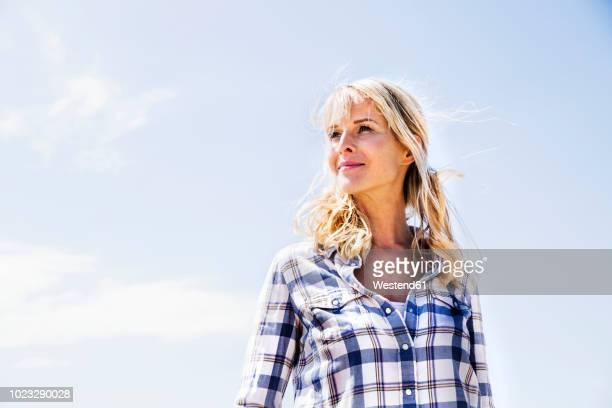 blond woman wearing checked shirt outdoors - donne di età media foto e immagini stock