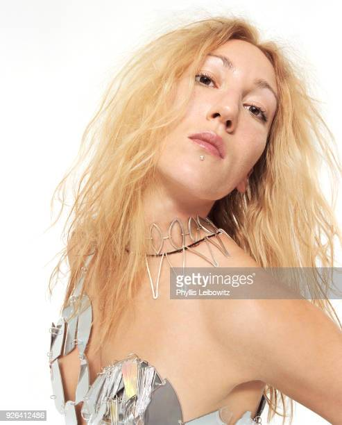 Blond woman wearing handcrafted dress made of CD pieces, fashion studio portrait
